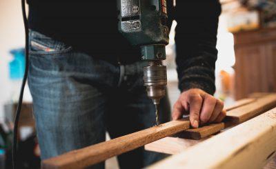 Homme qui perce une planche dans son atelier de bricolage