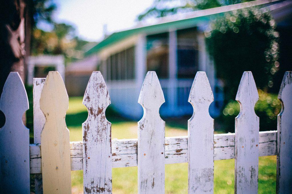 Vue d'une maison voisine depuis un portail en bois blanc