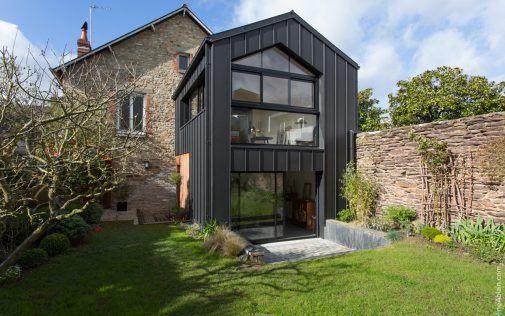 Une extension moderne à deux étages sur une maison en pierre