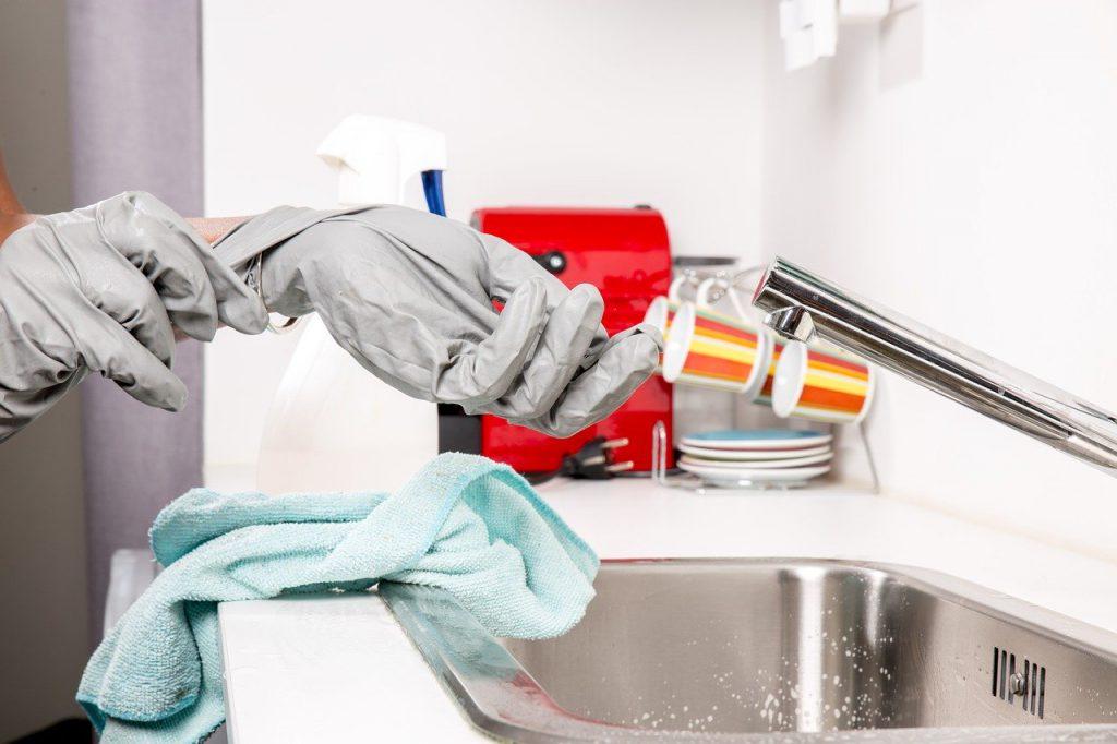 personne qui enfile des gants a coté de son lavabo