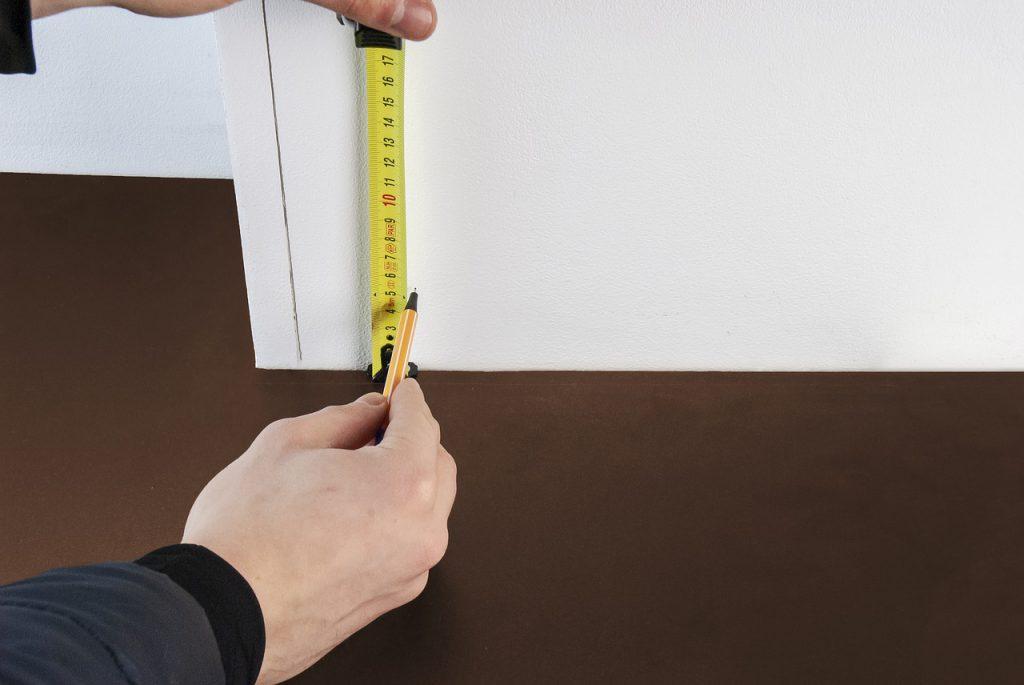 personne qui mesure une plinthe avant de la poser