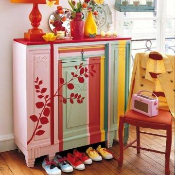 Buffet ancien en bois peint de rayures jaunes, roses et vertes