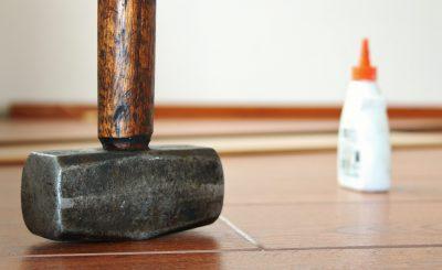marteau posé sur du parquet avec un tube de colle polymère en arrière-plan